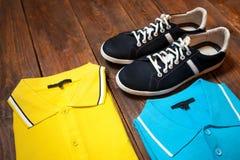 Insieme delle magliette variopinte degli uomini e delle scarpe di sport Fotografia Stock