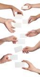 Insieme delle mani che tengono i biglietti da visita vuoti su bianco Fotografia Stock Libera da Diritti