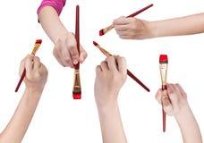 Insieme delle mani con i pennelli di arte con le punte rosse Fotografie Stock Libere da Diritti
