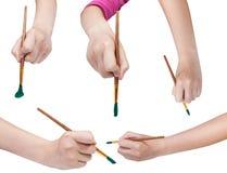 Insieme delle mani con i pennelli di arte con le punte verdi Fotografia Stock