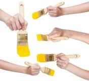 Insieme delle mani con il pennello piano con la punta gialla Immagini Stock