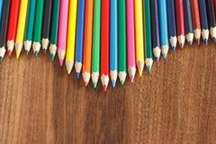 Insieme delle matite colorate, fondo di legno Fotografie Stock