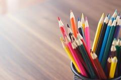Insieme delle matite colorate nel vetro, fondo di legno Fotografia Stock