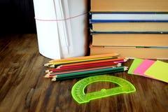 Insieme delle matite, degli autoadesivi, dei libri e del goniometro colorati fotografia stock