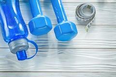 Insieme delle muto-campane blu della bottiglia di acqua di misura di nastro sul bordo di legno Immagine Stock Libera da Diritti