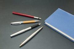 Insieme delle penne con un libro Fotografia Stock Libera da Diritti