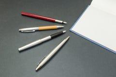 Insieme delle penne con un libro Immagini Stock