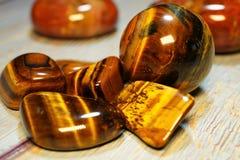 Insieme delle pietre preziose minerali naturali di certo tipo Tiger Eye Semiprecious Gemstone Birthstone su una tavola di legno U immagini stock