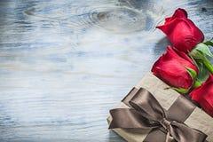Insieme delle rose rosse attuali avvolte della scatola sulla celebrazione del bordo di legno Fotografia Stock