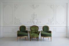 Insieme delle sedie d'annata di legno verdi che stanno nella parte anteriore gli elementi bianchi della parete di progettazione d Immagini Stock