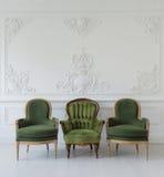 Insieme delle sedie d'annata di legno verdi che stanno nella parte anteriore gli elementi bianchi della parete di progettazione d Immagine Stock