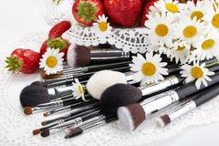 Insieme delle spazzole di trucco con le fragole ed i fiori Immagini Stock Libere da Diritti