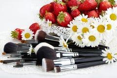 Insieme delle spazzole di trucco con le fragole ed i fiori Fotografia Stock Libera da Diritti