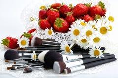 Insieme delle spazzole di trucco con le fragole ed i fiori Immagine Stock Libera da Diritti