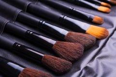 Insieme delle spazzole nere di trucco nella fila Fotografia Stock Libera da Diritti