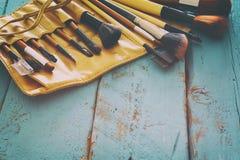 Insieme delle spazzole professionali di trucco sulla tavola di legno Fotografia Stock