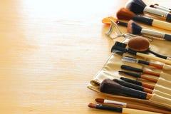 Insieme delle spazzole professionali di trucco sulla tavola di legno Immagini Stock