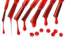 Insieme delle spazzole rosse e delle gocce dello smalto di chiodo Immagini Stock