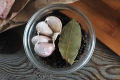 Insieme delle spezie in ciotola di vetro - aglio, pepe, foglia di alloro Immagine Stock