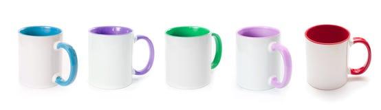 Insieme delle tazze bianche isolate su fondo bianco Immagine Stock
