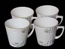 Insieme delle tazze bianche isolate sul nero Fotografie Stock