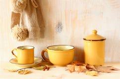 Insieme delle tazze da caffè d'annata e del barattolo sopra la tavola e le foglie di autunno di legno strutturate rustiche l'imma Fotografia Stock Libera da Diritti