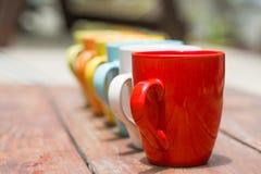 Insieme delle tazze variopinte della tazza su una vecchia tavola di legno Immagini Stock