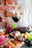 Insieme dello spuntino del vino Vetro di vino rosso, dell'uva e di vari chees di specie Immagini Stock