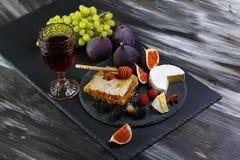 Insieme dello spuntino e del vino miele, vetro di vino rosso, fichi, uva, dadi, varietà del formaggio, aperitivi e bacche sul bor fotografia stock