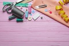 Insieme di adattamento gli strumenti, gli accessori e del tessuto sulla tavola, fotografia stock