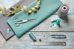 Insieme di adattamento gli strumenti, gli accessori e del tessuto sulla tavola, immagini stock