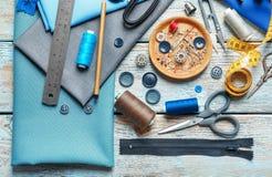 Insieme di adattamento gli strumenti, gli accessori e del tessuto sulla tavola, fotografie stock