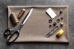 Insieme di adattamento gli strumenti, gli accessori e del tessuto sulla tavola immagini stock