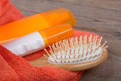 Insieme di bagno degli accessori - asciugamano, spazzola per i capelli e cosmetici arancio per viziare sul fondo di legno Immagine Stock