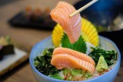 Insieme di color salmone del sashimi con i bastoncini che tengono un pezzo di sal affettato Fotografia Stock Libera da Diritti