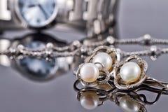 Insieme di gioielli d'argento con le perle e gli orologi delle donne Fotografie Stock