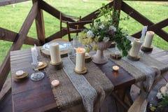 Insieme di legno della tavola con le candele ed i fiori all'aperto immagine stock