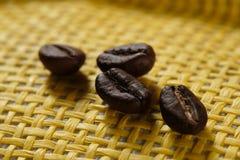 Insieme di macro chicchi di caffè arrostiti freschi, fondo giallo del canestro di vimini Immagine Stock