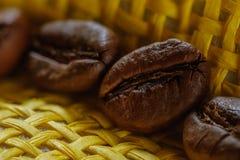 Insieme di macro chicchi di caffè arrostiti freschi, fondo giallo del canestro di vimini Immagini Stock