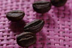 Insieme di macro chicchi di caffè arrostiti freschi, fondo rosa di vimini rosa Fotografia Stock
