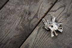 Insieme di nuove chiavi del metallo su legno invecchiato Fotografie Stock Libere da Diritti