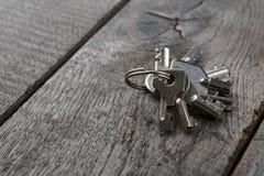 Insieme di nuove chiavi del metallo su legno invecchiato Fotografia Stock Libera da Diritti