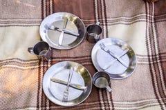 Insieme di picnic, tre persone metal la coltelleria, il termos, i piatti, tazze di tè plaid e tovagliolo marroni dal lago nei pre fotografia stock libera da diritti