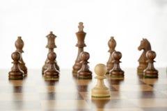 Insieme di scacchi di legno, pegno bianco di fronte al gruppo nemico nero a bordo Fotografia Stock