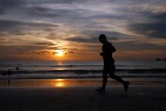 Insieme di Sun della siluetta che funziona sulla spiaggia Fotografia Stock Libera da Diritti