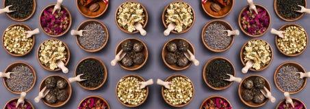 Insieme di tè asciutto differente in ciotola di legno fotografie stock