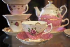 Insieme di tè floreale di CanPink della ragazza della tenuta dei rifiuti disgustati del metallo su vetro Fotografia Stock