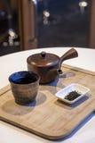 Insieme di tè giapponese con la foglia di tè sul vassoio di legno Fotografia Stock