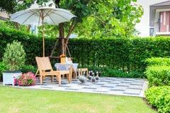 Insieme di tè su un banco di pietra in un giardino floreale Fotografie Stock Libere da Diritti