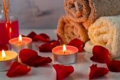 Insieme di trattamento della stazione termale con olio profumato, le candele, i petali rosa ed i fiori fotografia stock libera da diritti